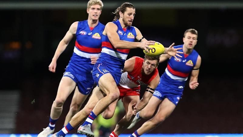 Marcus Bontempelli (c) has inspired the Bulldogs to a 28-point AFL victory over Sydney Swans