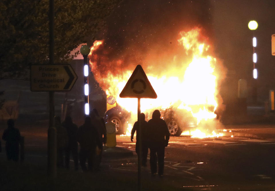 Masked loyalists are seen after hijacking and setting a car on fire at the Cloughfern roundabout in Newtownabbey, Belfast, Northern Ireland, Saturday, April 3, 2021. Masked men threw petrol bombs and hijacked cars in the Loyalist area North of Belfast. Loyalists and unionists are angry about post-Brexit trading arrangements which they claim have created barriers between Northern Ireland and the rest of the UK. (Peter Morrison/PA via AP)