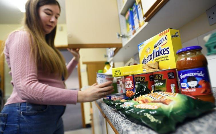 Woman picking up a container from a shelf of food at a food bank