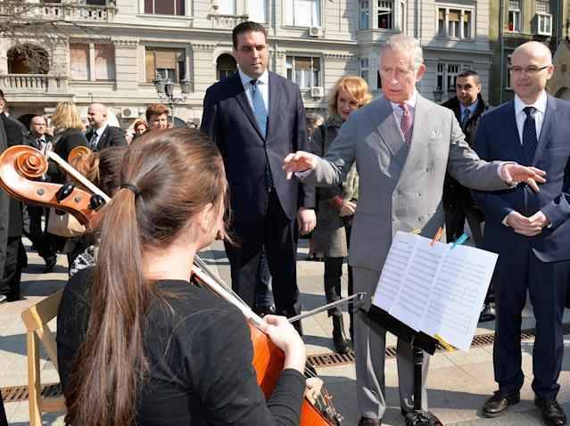 Prince Charles listening to a chamber orchestra perform on a market square during a visit to Serbia. (Getty Images)