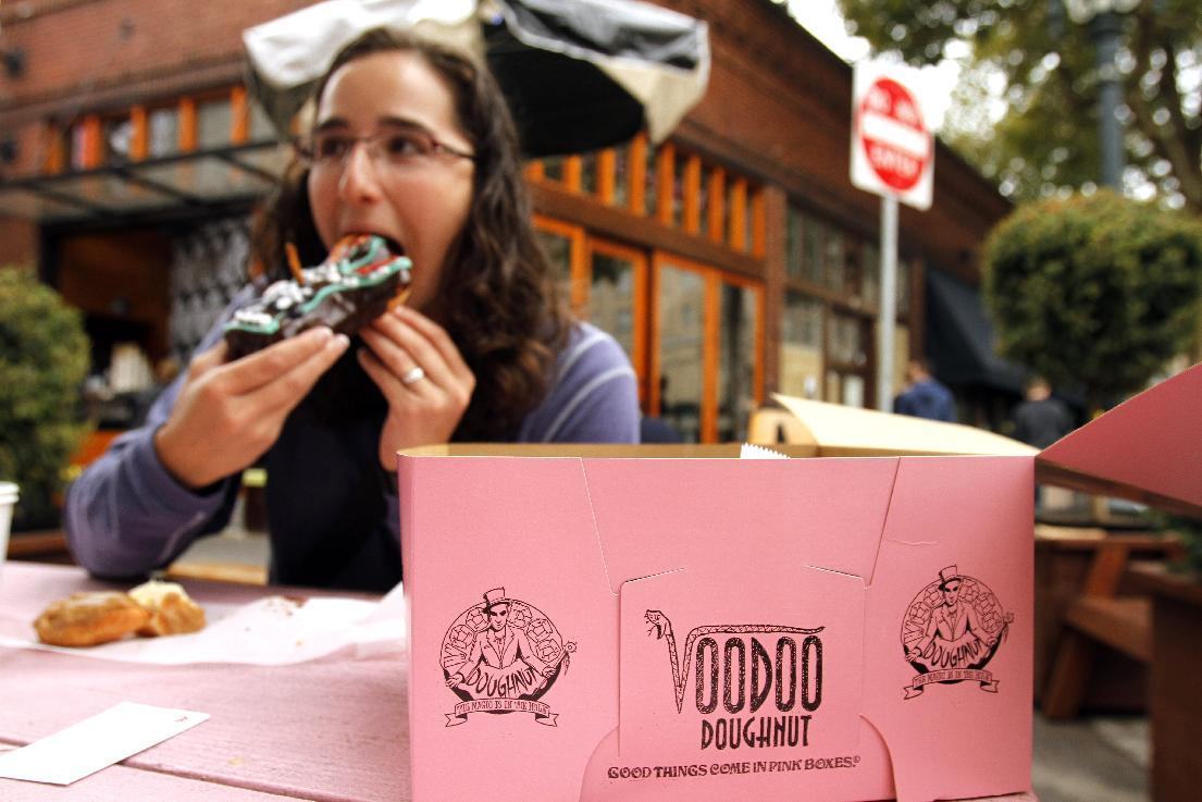 Jennie Myren, who is from Iowa and spending her honeymoon in Portland, enjoys the signature doughnut shaped like a voodoo doll with a pretzel stick stake through its' heart outside the famous Voodoo Doughnuts shop in downtown Portland, Ore., Wednesday, Sept. 19, 2012. Researchers at Portland State University found that the Portland atmosphere and culture is a magnet for the young and college educated, even though a disproportionate share of them are working in part-time jobs or positions that don't require a college degree. (AP Photo/Don Ryan)