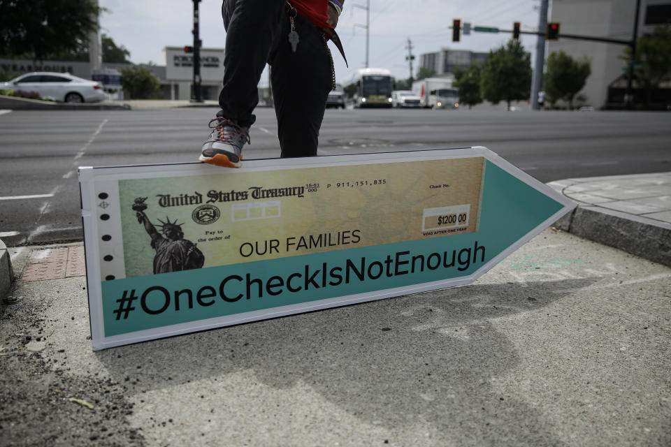 Jeremiah Miller, 17, of Atlanta, leans on a large check sign for the #OneCheckIsNotEnough campaign near Georgia Senator David Perdue's office on Tuesday, Aug. 11, 2020, in Atlanta. The campaign said the large check is to urge politicians to support recurring direct payments in the next coronavirus relief package. (AP Photo/Brynn Anderson)