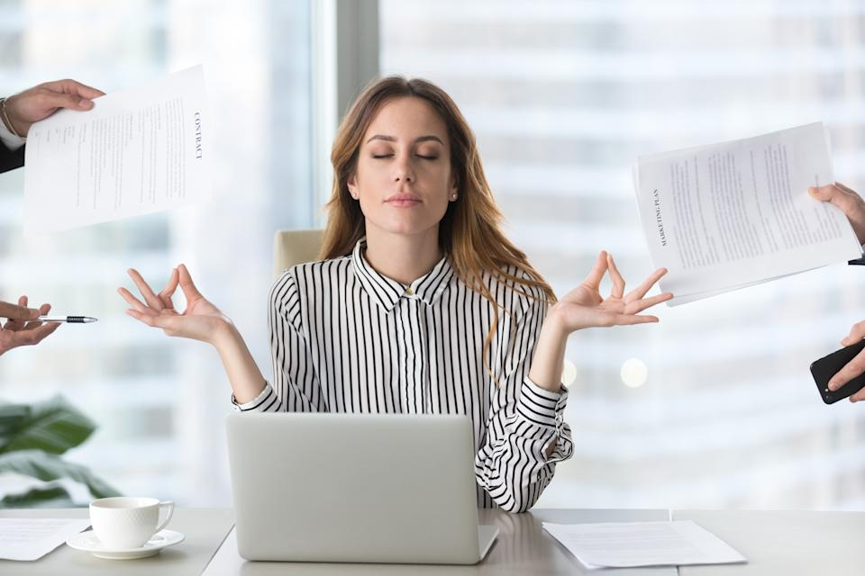 Female executive meditating at work for mental balance.
