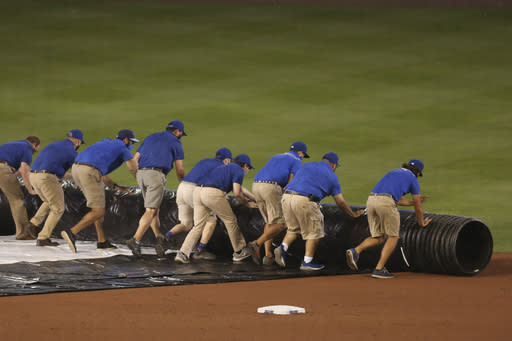 Members of the Toronto Blue Jays' grounds crew roll out the tarp to cover the field during the fourth inning of the team's baseball game against the Tampa Bay Rays, Saturday, Aug. 15, 2020, in Buffalo, N.Y. (AP Photo/Jeffrey T. Barnes)