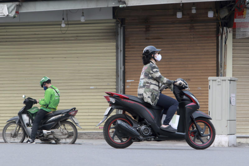 Motorcyclists drive past closed shops in Hanoi, Vietnam, Friday, March 27, 2020. Vietnam's Prime Minister Nguyen Xuan Phuc has ordered to shut down non-essential business to curb the spread of COVID-19. The new coronavirus causes mild or moderate symptoms for most people, but for some, especially older adults and people with existing health problems, it can cause more severe illness or death. (AP Photo/Hau Dinh)
