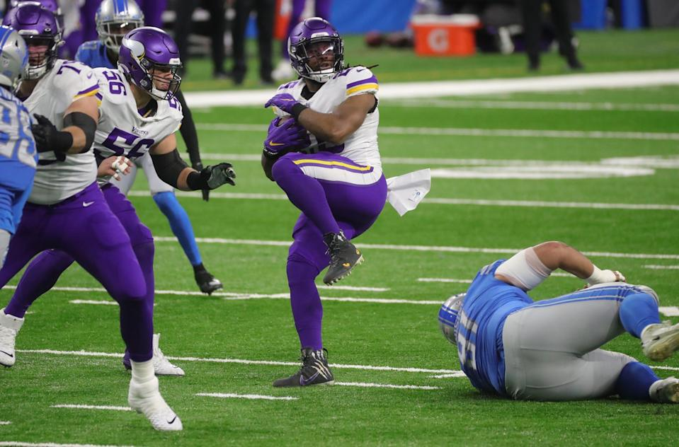 Minnesota Vikings running back Alexander Mattison goes over Detroit Lions defensive tackle John Penisini, right, during the first half at Ford Field, Sunday, Jan. 3, 2021.