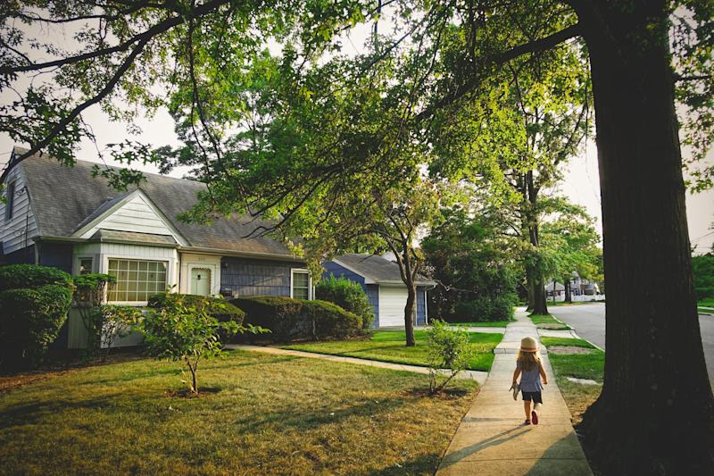A little girl walking down the sidewalk past a house at sunset.