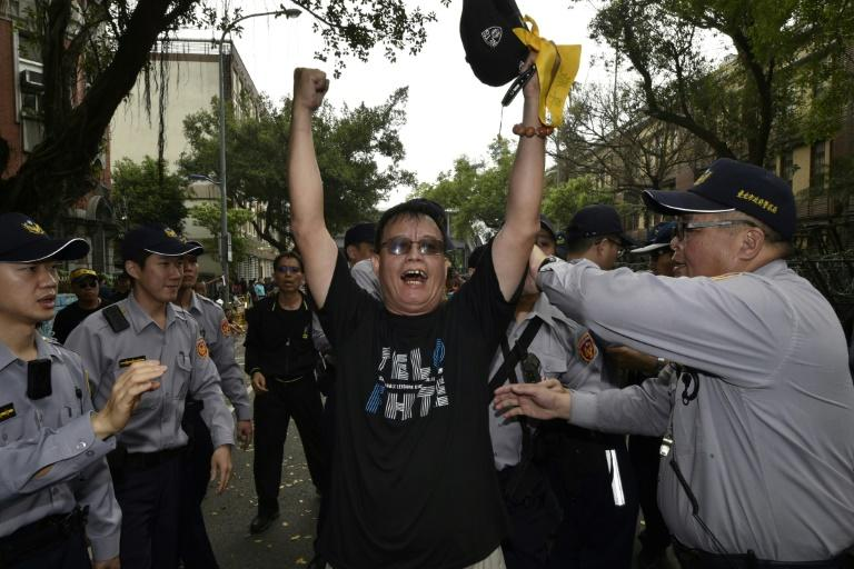 Police surround a protester outside  parliament during an anti-pension reform demonstration in Taipei on April 19, 2017