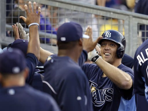 Tampa Bay Rays' Shelley Duncan, right, smiles as he receives high-fives from teammates in the dugout after his solo home run in the second inning of an exhibition spring training baseball game against the Pittsburgh Pirates in Port Charlotte, Fla., Monday, March 25, 2013. (AP Photo/Elise Amendola)