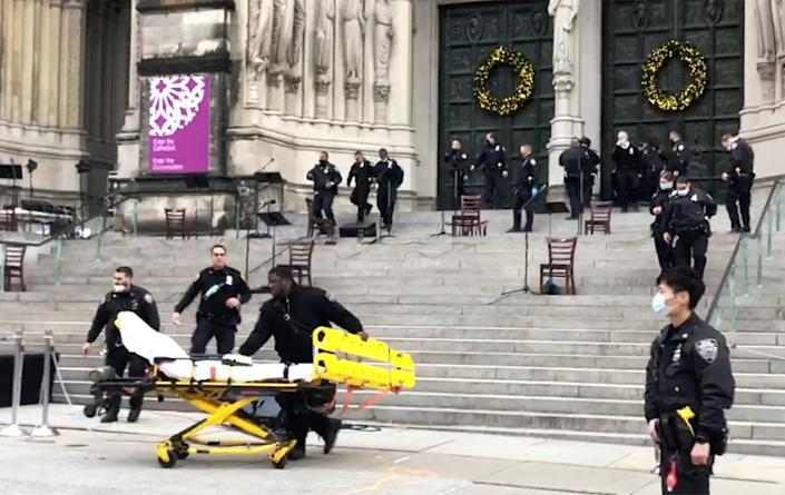 Emergency medical personnel pull a stretcher up to the scene of a shooting at the Cathedral Church of St. John the Divine, Sunday, Dec. 13, 2020, in New York.