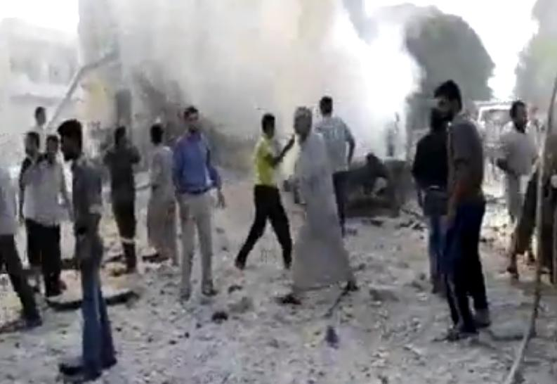 In this image made from amateur video released by the Shaam News Network and accessed Tuesday, Aug. 28, 2012, Syrian men stand near smoke rising from buildings due to shelling in Kfarnebel, Idlib province, northern Syria. (AP Photo/Shaam News Network via AP video) THE ASSOCIATED PRESS IS UNABLE TO INDEPENDENTLY VERIFY THE AUTHENTICITY, CONTENT, LOCATION OR DATE OF THIS HANDOUT PHOTO