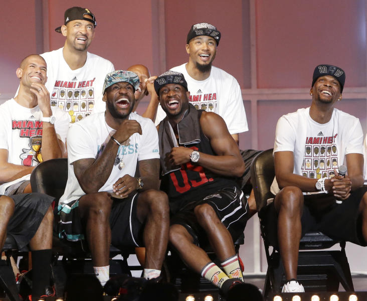 Miami Heat players laugh as they watch highlights of center Chris Bosh, right, Monday, June 24, 2013, during a celebration for season ticket holders at the American Airlines Arena in Miami. Other players from left are: Shane Battier, Juwan Howard, LeBron James, Dwyane Wade and Rashard Lewis. The Heat defeated the San Antonio Spurs 95-88 in Game 7 to win their second straight NBA championship. (AP Photo/Wilfredo Lee)