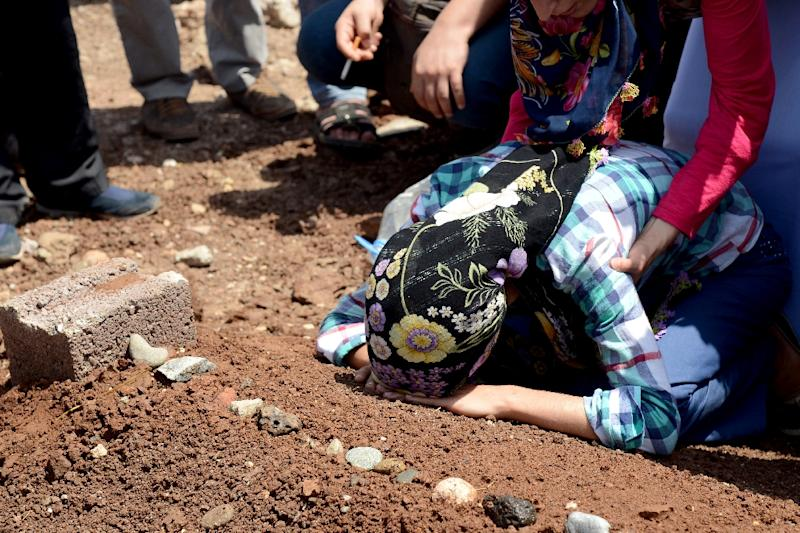 A woman mourns over the grave of a fighter of the Kurdish People's Protection Units following a funeral in Diyarbakir in southeastern Turkey, after the bodies of 13 militants were repatriated from Iraq, August 5, 2015 (AFP Photo/Ilyas Akengin)