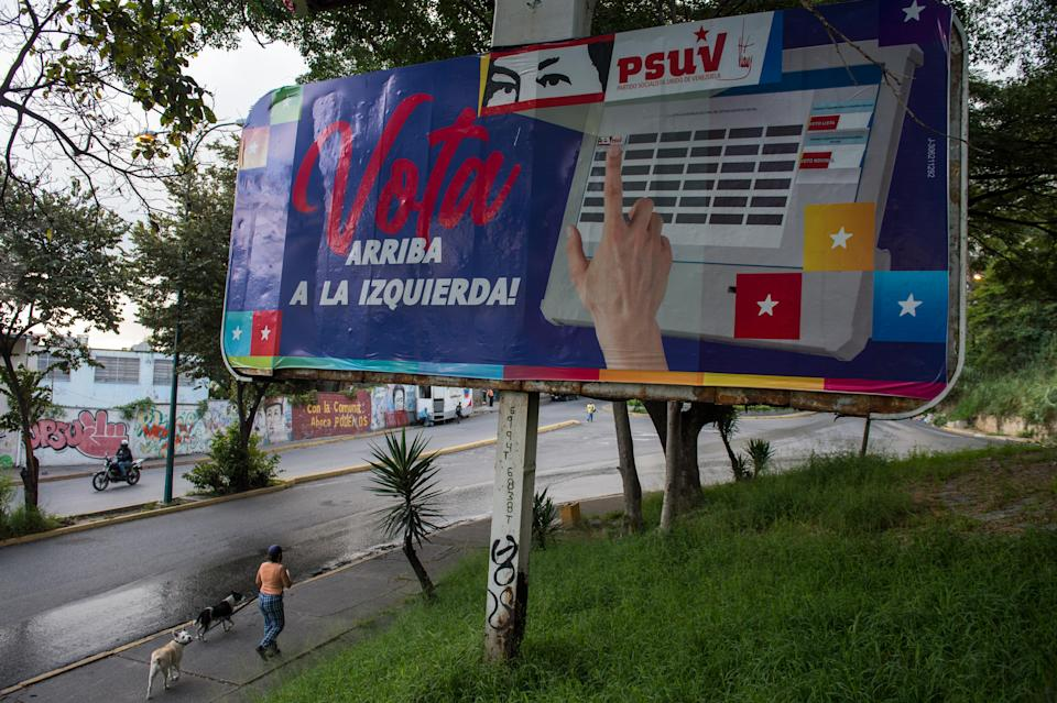 People walk near political propaganda depicting the eyes of late Venezuelan President Hugo Chavez, in Caracas on December 2, 2020 ahead of parliamentary elections in the country. - Venezuelan will hold legislative elections on December 6. (Photo by Cristian Hernandez / AFP) (Photo by CRISTIAN HERNANDEZ/AFP via Getty Images)