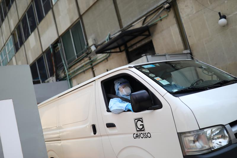 Employees of Funeral Gayosso wearing protective clothing drive a vehicle while they go to transport a deceased person, as the outbreak of the coronavirus disease (COVID-19) continues in Mexico City, Mexico May 11, 2020. Picture taken May 11, 2020. REUTERS/Edgard Garrido