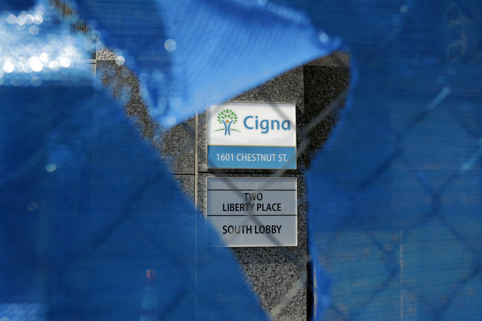 The Cigna logo is seen behind a construction fence, Friday, March 9, 2018, in Philadelphia. The insurer Cigna will acquire the nation's biggest pharmacy benefit manager, Express Scripts, the latest in a string of proposed tie-ups as health care's bill payers attempt to get a grip on rising costs. Cigna CEO David Cordani said Thursday, March 8, that the combined company will make health care more simple for customers. (AP Photo/Matt Slocum)