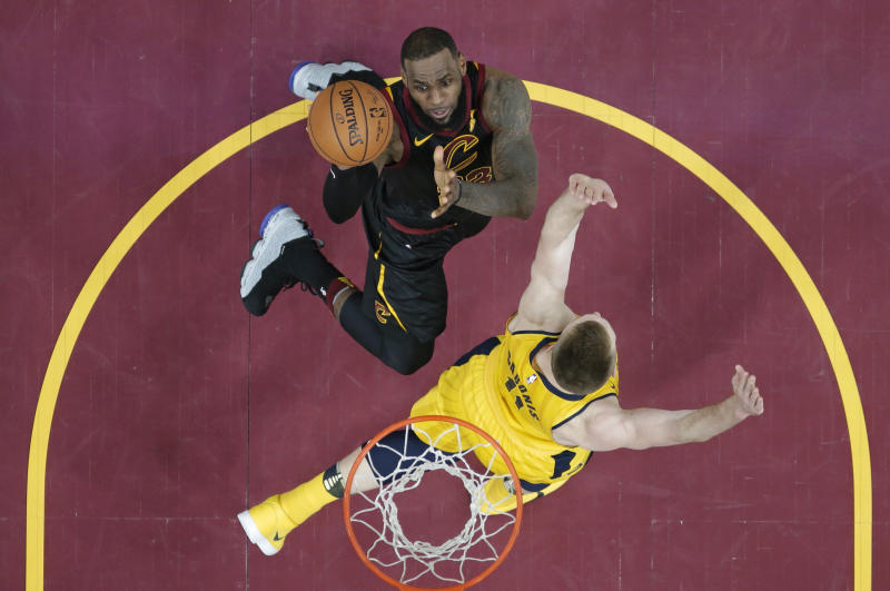 Cleveland Cavaliers' LeBron James, top, drives against Indiana Pacers' Domantas Sabonis, from Lithuania, in the first half of Game 1 of an NBA basketball first-round playoff series Sunday, April 15, 2018, in Cleveland. (AP Photo/Tony Dejak)