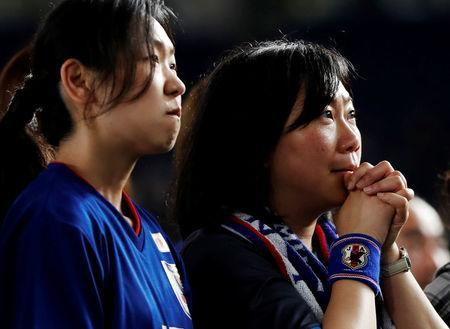 Japanese soccer fans react as they watch a broadcast of the World Cup Group H soccer match Colombia vs Japan, at a public viewing event in Tokyo, Japan June 19, 2018. REUTERS/Issei Kato