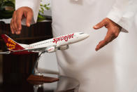 An Emirati man reaches out for a model of a SpiceJet airliner in Ras al-Khaimah, United Arab Emirates, Wednesday, Oct. 23, 2019. India's low-cost airline SpiceJet announced plans Wednesday to build its first international hub in the United Arab Emirates, offering a pledge of support to Boeing Co. by saying it would use now-grounded 737 MAX aircraft in the operation once regulators approve the planes for flight. (AP Photo/Jon Gambrell)