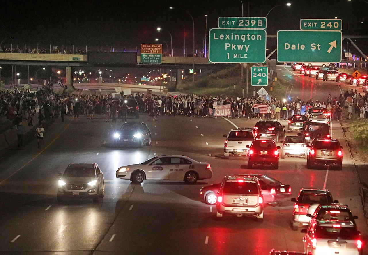 <p>Demonstrators hold signs as they as they block traffic on Interstate 94 in St. Paul, Minn., after leaving a vigil at the state Capitol on Friday, June 16, 2017. A Minnesota police officer was cleared Friday in the fatal shooting of Philando Castile, a black motorist whose death captured national attention when his girlfriend streamed the grim aftermath on Facebook. (Anthony Souffle/Star Tribune via AP) </p>