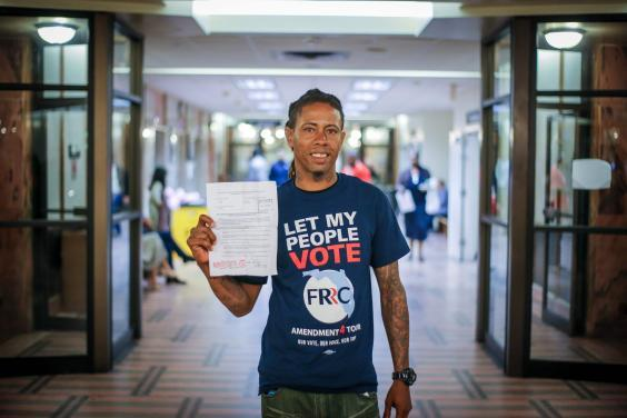 Michael Monfluery, a 38-year-old who has never been eligible to vote, shows off a certificate restoring his right after the special court hearing in Miami, Florida last month (Zak Bennett/AFP via Getty Images)