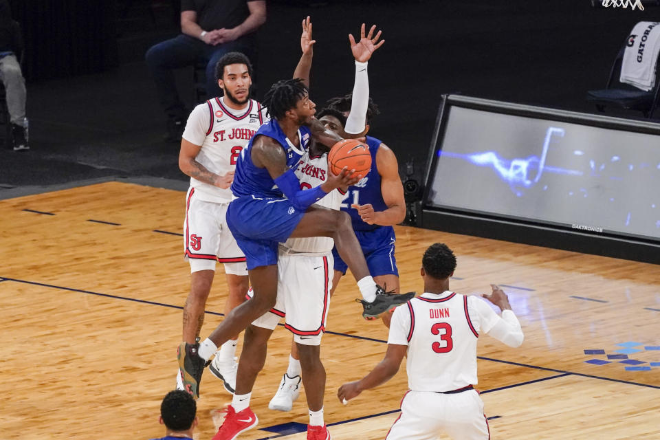 Seton Hall guard Myles Cale, center, goes to the basket against St. John's forward Marcellus Earlington (10) during the second half of an NCAA college basketball game in the quarterfinals of the Big East conference tournament, Thursday, March 11, 2021, in New York. (AP Photo/Mary Altaffer)