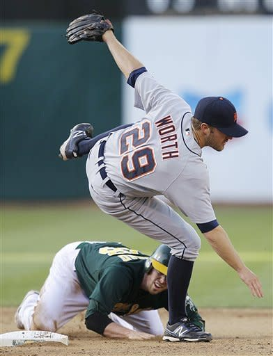 Detroit Tigers second baseman Danny Worth (29) struggles to maintain his balance over Oakland Athletics' Eric Sogard after completing a double play during the seventh inning of a baseball game, Saturday, May 12, 2012, in Oakland, Calif. Athletics' Brandon Inge was out at first base. (AP Photo/Ben Margot)