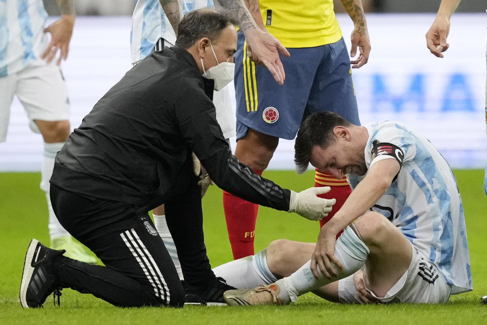 Argentina's Lionel Messi is treated after being fouled by Colombia's Frank Fabra during a Copa America semifinal soccer match at the National stadium in Brasilia, Brazil, Tuesday, July 6, 2021. (AP Photo/Andre Penner)