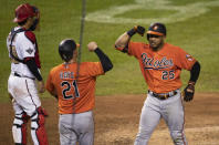 Baltimore Orioles' Anthony Santander (25) and Austin Hays (21) celebrate with an elbow-bump after Santander hit a three-run home run during the eighth inning of the team's baseball game against the Washington Nationals in Washington, Saturday, Aug. 8, 2020. Nationals catcher Kurt Suzuki is at left. The Orioles won 5-3. (AP Photo/Manuel Balce Ceneta)