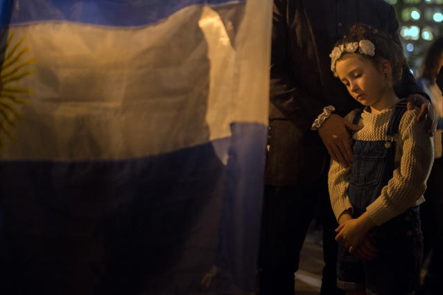 <p>A child reacts as a woman holds an Argentinian flag next to her during a candle light walk to remember the victims of the recent truck attack near the crime scene on Thursday, Nov. 2, 2017, in New York. (Photo: Andres Kudacki/AP) </p>