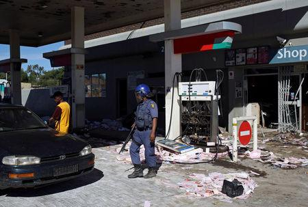 A Police officer stands guard after a filling station was looted by protesters in Mahikeng