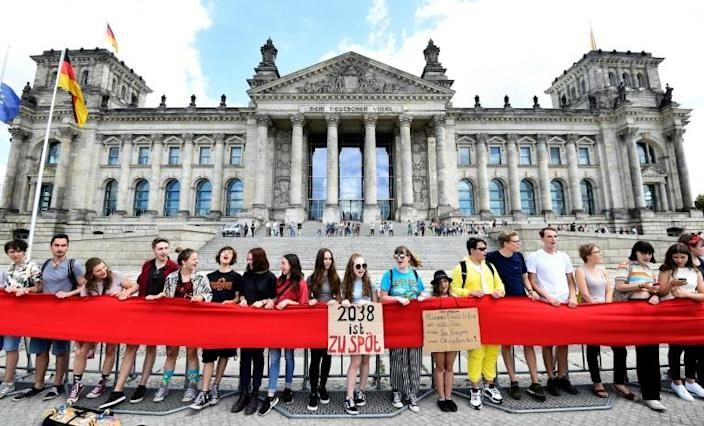 """Activists stretched a bolt of red cloth from hand to hand while holding signs with messages like """"2038 is too late"""" (AFP Photo/Tobias SCHWARZ )"""