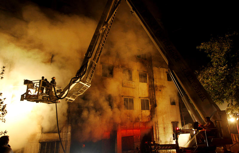 FILE - In this Saturday, Nov. 24, 2012 file photo, Bangladeshi firefighters battle a fire at a garment factory in the Savar neighborhood in Dhaka, Bangladesh, late. A Dhaka fire official said the Tazreen factory's fire safety certification had expired on June 30, and fire officials refused to renew it because the building did not have the proper safety arrangements. The factory did not have any fire exits for its 1,400 workers, many of whom became trapped by the blaze. Investigators said the death toll would have been far lower if there had been even a single emergency exit.  (AP Photo/Hasan Raza)