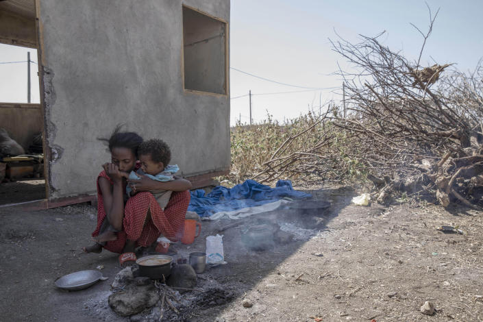 """Bethlehem, 21, an ethnic Tigrayan survivor from Mai-Kadra, Ethiopia, kisses her daughter's hand as she cooks for her family inside a temporary shelter at Village 8, the transit center near the Lugdi border crossing, eastern Sudan, Nov. 22, 2020. Witnesses say hundreds of civilians were slaughtered in Mai-Kadra, but they disagree about who killed whom. """"Anyone they found, they would kill,"""" said Tesfaalem Germay, Bethlehem's husband, speaking of Ethiopian federal and Amhara regional forces. He said he saw hundreds of bodies. Others say it was Tigrayan forces and their allies who were responsible. (AP Photo/Nariman El-Mofty)"""