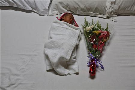 Gabriella, the week-old daughter of Rekha Patel, 42, and Daniele Fabbricatore, 39, sleeps in a hotel room in Anand town, about 70 km (44 miles) south of the western Indian city of Ahmedabad August 26, 2013. REUTERS/Mansi Thapliyal