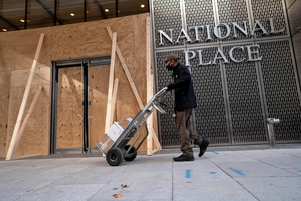 WASHINGTON, D.C., Nov. 19, 2020 -- A delivery worker walks past an office building boarded up with plywood in Washington D.C., the United States, on Nov. 19, 2020. The number of initial jobless claims in the United States rose to 742,000 last week, as the labor market recovery slows amid surging COVID-19 cases, the Labor Department reported on Thursday. (Photo by Liu Jie/Xinhua via Getty) (Xinhua/Liu Jie via Getty Images)