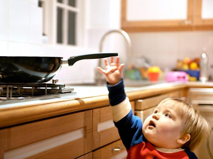 A child reaches for a hot pan on a stove.