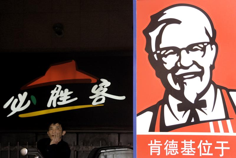 FILE - In this Thursday April 5, 2007, file photo, a man stands in front of the signs of KFC and Pizza Hut restaurant in Shanghai, China. The owner of the Taco Bell, Pizza Hut and KFC chains predicted Wednesday, Oct. 10, 2012, its fast-growing China business will serve up another round of strong profit growth next year despite a slowing economy in its most important overseas market. Yum Brands Inc. executives also foreshadowed more menu rollouts in the coming year at its flourishing Taco Bell business in the U.S.(AP Photo/Eugene Hoshiko, File)