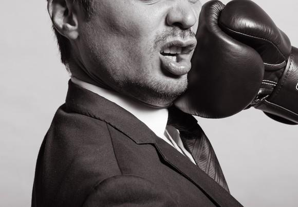 Businessman being punched in the face by a glove