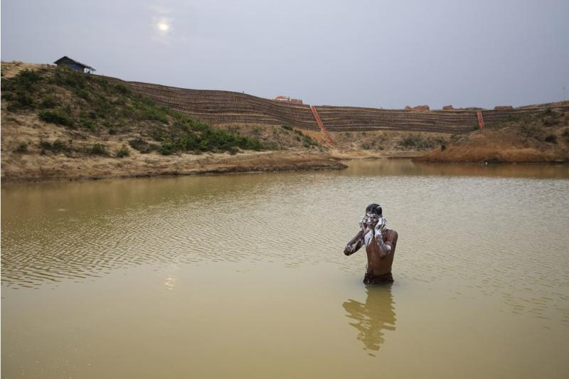 A man bathes in a man-made pond near the camp where he lives. Behind him is the construction of the Camp 20 Extension. | James Nachtwey for TIME