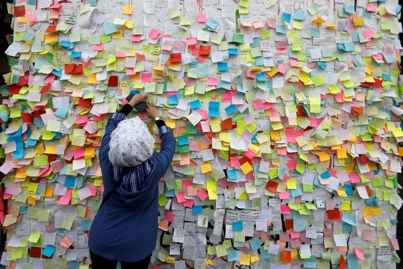 An Iraqi woman demonstrator pastes a note with her wish at a wall of wishes, during ongoing anti-government protests, at the building called 'the Turkish Restaurant Building', in Baghdad