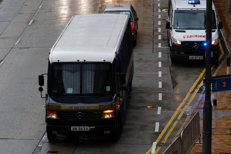 A prison van arrives as police stand guard for Tong Ying-kit's arrival, the first person charged under a new national security law, in Hong Kong