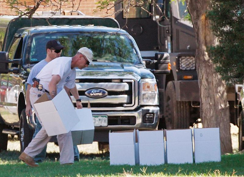 "An ATF agent arranges boxes for evidence in front of the apartment of James Holmes in Aurora, Colo., Saturday, July 21, 2012.  Federal authorities detonated one small explosive and disarmed another inside Holmes' apartment, but several other explosive devices remained, said Aurora police Sgt. Cassidee Carlson. Twelve people were killed and dozens were injured in a shooting attack early Friday at a packed movie theater during a showing of the Batman movie, ""The Dark Knight Rises.""   Police have identified Holmes, 24, as the suspected shooter. (AP Photo/Ed Andrieski)"