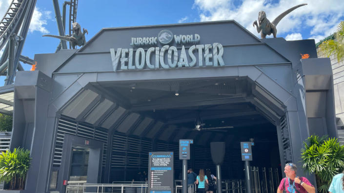 The gray entrance of the VelociCoaster, flanked by two raptor statues