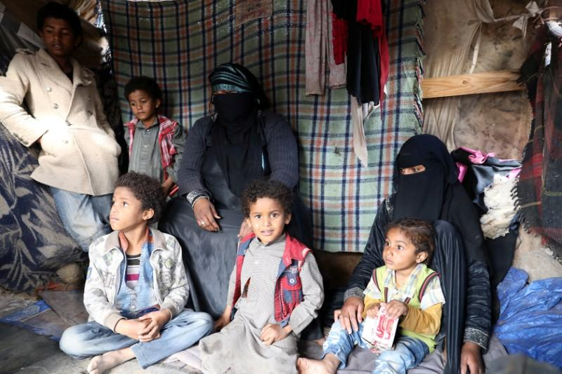 Sameera Hussein Nasser, 40, sits with her children at a hut where they live at a camp for internally displaced people near Sanaa