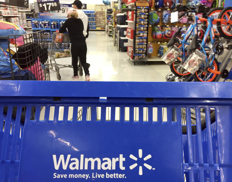 FILE - In this June 5, 2017, file photo, customers shop for food at Walmart in Salem, N.H. Walmart says it will no longer sell firearms and ammunition to people younger than 21. The retailer's new policy comes after Dick's Sporting Goods announced earlier Wednesday, Feb. 28, 2018, that it would restrict the sale of firearms to those under 21 years old. It didn't mention ammunition. Walmart says the decision came after a review of its firearm sales policy in light of the mass shooting at a high school in Parkland, Florida. (AP Photo/Elise Amendola, File)
