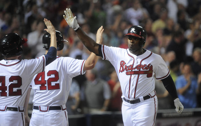 Atlanta Braves' Justin Upton, right, is congratulated as he comes back to the dugout after a home run against the Kansas City Royals during the eighth inning of a baseball game, Tuesday, April 16, 2013, in Atlanta. Atlanta won 6-3. (AP Photo/John Amis)