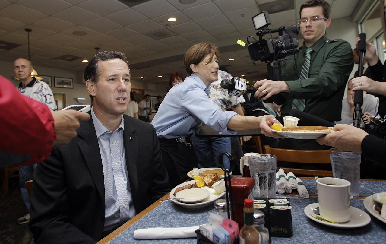 Republican presidential candidate, former Pennsylvania Sen. Rick Santorum is served breakfast as he talks to the media during a campaign stop at McElroy's On the Bayou, Monday, March 12, 2012, in Ocean Springs, Miss. (AP Photo/Eric Gay)