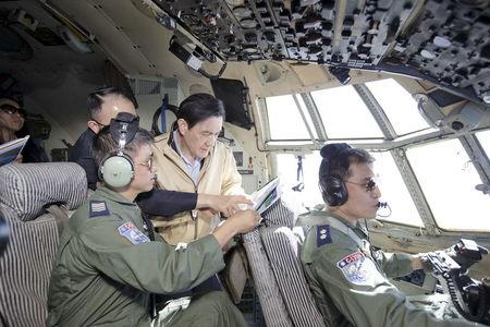 Taiwan's President Ma Ying-jeou (C) reads a document on a C-130 airplane on the way to the disputed Itu Aba or Taiping island in the South China Sea, January 28, 2016. REUTERS/Chen Chien Hsing/Presidential Office/HandoutA