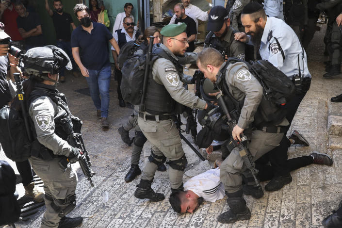 Israeli police officers detain a Palestinian youth during a protest against Israel's air strikes on the Gaza Strip and the violent confrontations between Israeli security forces and Palestinians, in Jerusalem's Old City, Tuesday, May 18, 2021. (AP Photo/Mahmoud Illean)